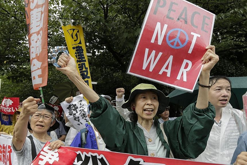"Japan's Premier Shinzo Abe wants to put in place a security framework that will allow the Self Defence Force (above) to take part in military operations with the US and other countries. But huge rallies have been held against the ""war Bills"", such as"