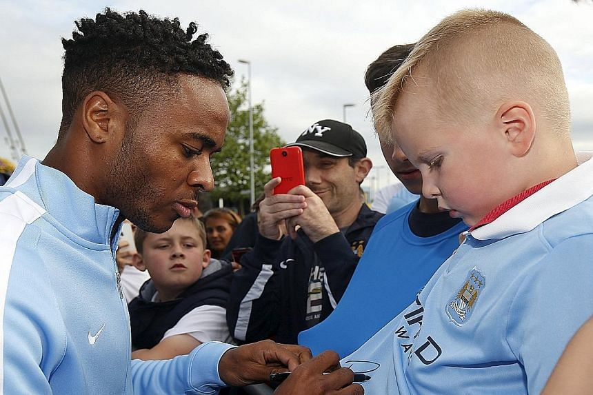 Raheem Sterling signing autographs for supporters on Tuesday, after joining Manchester City. The forward rejected contract offers of £100,000 a week from Liverpool and joined City for £49 million.