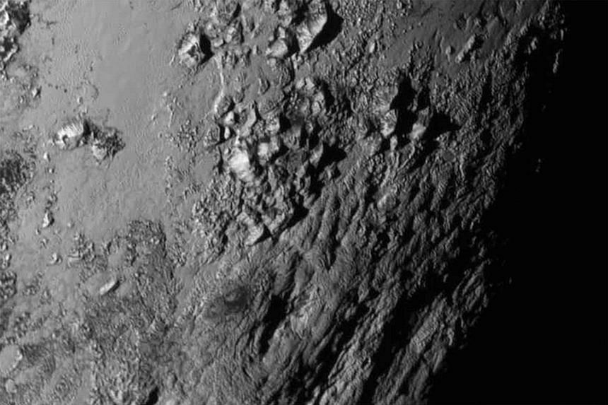 A handout from Nasa (far left) shows Pluto and its largest moon Charon in false colour image. Charon is shown to have canyons and cliffs. A close-up image (left) from Nasa of a region near Pluto's equator reveals a giant surprise: a range of youthful