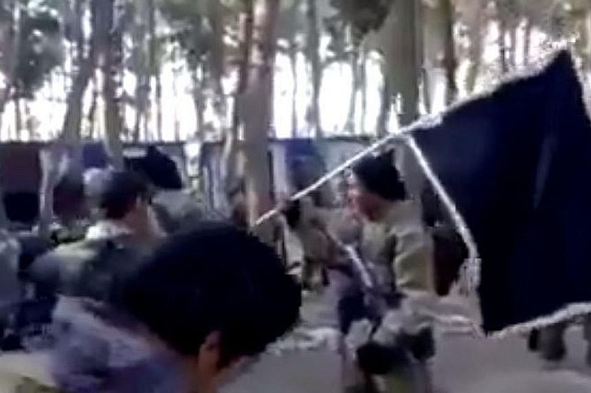 A screenshot from the video clip showing Indonesian-speaking men in military fatigues and armed with rifles preparing for a field assignment. The clip is the latest to show the existence of the Malay archipelago unit for ISIS.