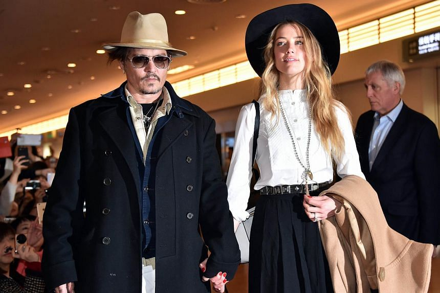 Actor Johnny Depp (left) and wife Amber Heard arriving at Tokyo International Airport.