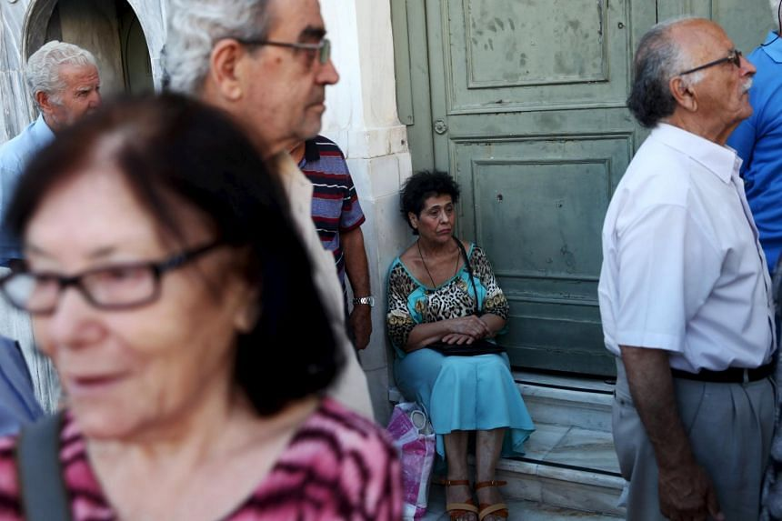 Pensioners wait to receive part of their pensions at a National Bank branch in Athens on July 16, 2015.