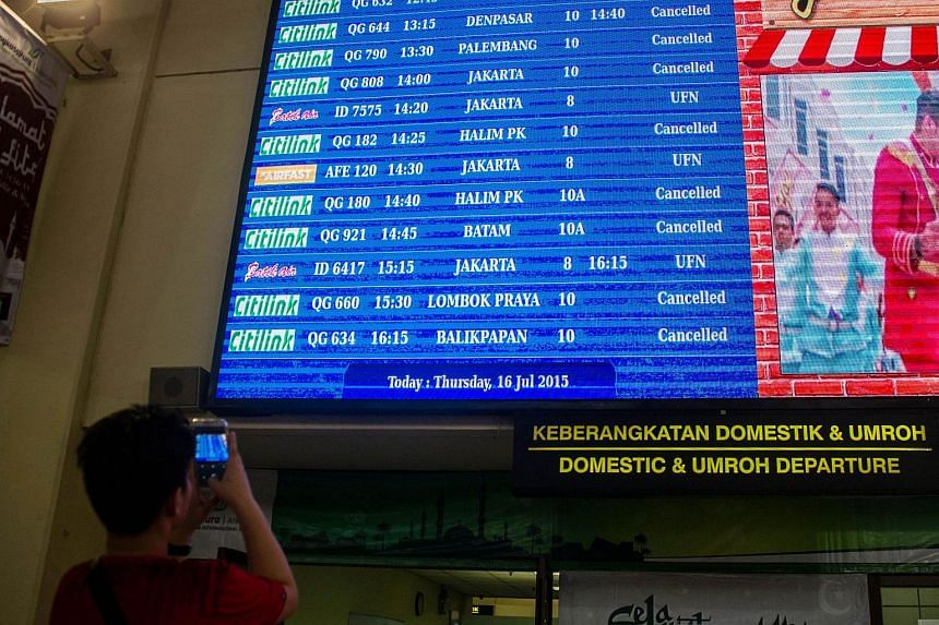 A passenger taking a picture of a display board showing cancelled flights at Juanda airport.