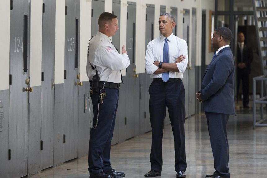 The US President tours a cell block with  Charles Samuels (right), Bureau of Prisons director, and correctional officer Ronald Warlick.