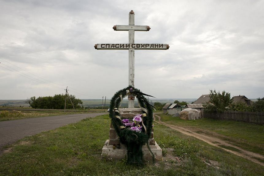 """A wreath is placed on a cross with an inscription that reads """"Save and protect"""" next to the site where MH17 was downed in eastern Ukraine."""