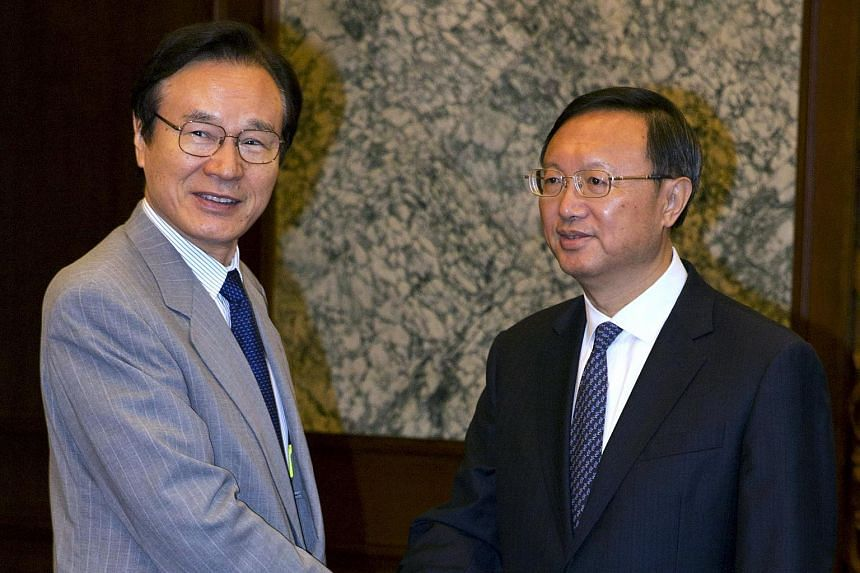 Japanese National Security Adviser Shotaro Yachi (left) shakes hands with Chinese State Councilor Yang Jiechi during a meeting at the Diaoyutai State guesthouse in Beijing on July 16, 2015.
