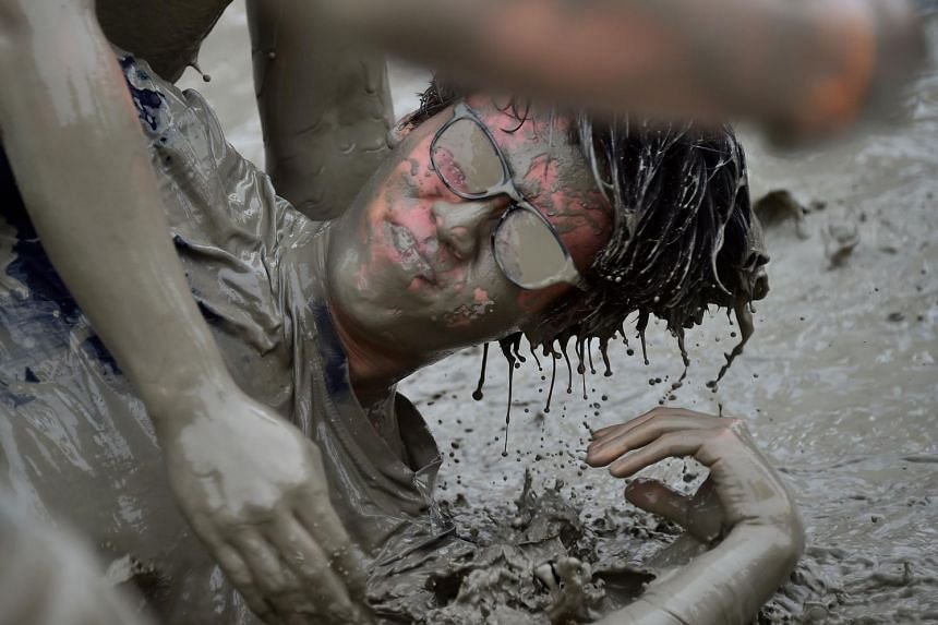 Tourists play with mud during the 18th Boryeong mud festival at Daecheon swimming beach in Boryeong, 150 kilometers southwest of Seoul on July 18, 2015.
