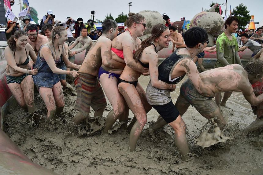 Tourists play with mud during the 18th Boryeong mud festival at Daecheon swimming beach in Boryeong, 150 kilometers southwest of Seoul, on July 18, 2015.