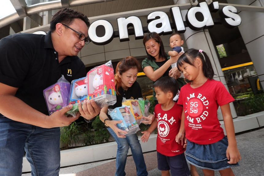 From left) McDonald's marketing executive Albert Umali and senior marketing manager Jassie Ling hand out the limited edition SG50 Hello Kitty set, containing six different designs of the plush collectibles, to Madam Rosalind Goh, 35, and her children