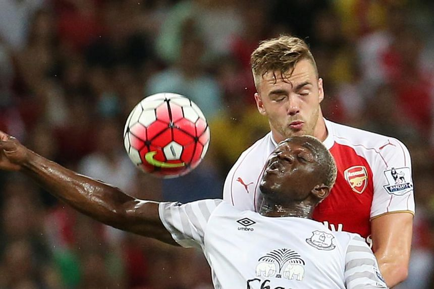 Arsenal's Calum Chambers (left) in action against Arouna Kone of Everton (right).