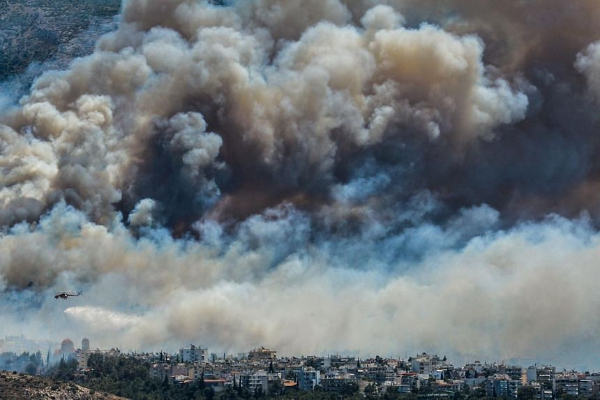 An airplane of firefighters flies over smokes billowing over Athens, on July 17, 2015 as firemen were battling a brush fire in northeastern Athens and another wildfire in the southern Pelopponese peninsula that prompted the evacuation of five village