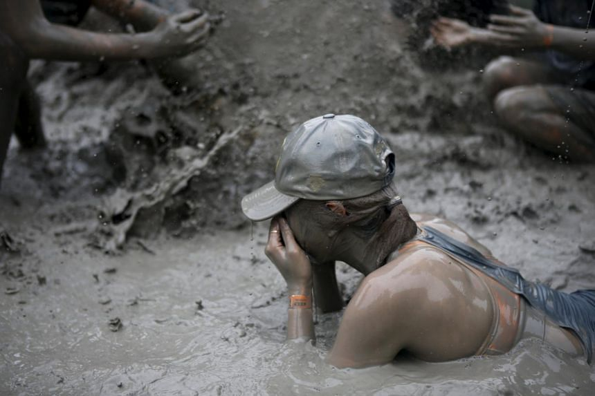 Tourists play in a mud pool during the Boryeong Mud Festival at Daecheon beach in Boryeong, South Korea on July 18, 2015.