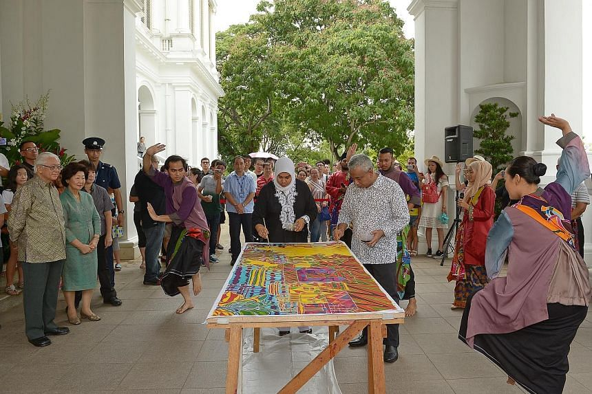 Artist Ika Zahri Sarkasi and his wife, Madam Zarinah Begum, painting a batik piece in the presence of President Tony Tan Keng Yam and his wife Mary at the Istana Open House yesterday in celebration of Hari Raya Puasa. The artists were joined by Malay