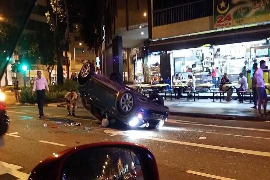 The Mini Cooper ended upside down after crashing into a parked car. The Mini's female driver was taken conscious to hospital along with the driver of the parked Toyota Vios. A passer-by is also believed to have been hurt.