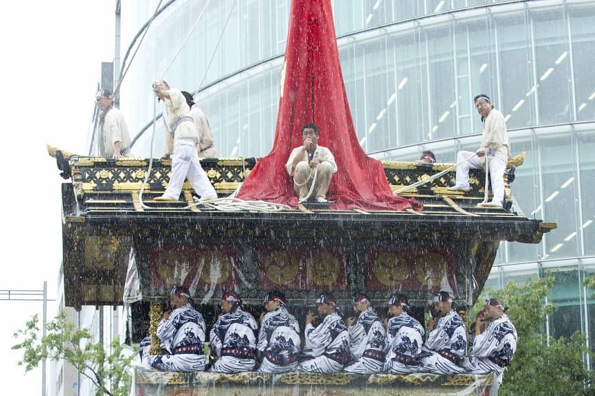 Enduring the torrential rain brought on by Typhoon Nangka, Kyoto residents in traditional samurai-era costumes participate in the city's historical Gion festival yesterday in the downtown area.