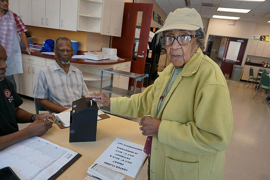 Ms Corrine Whoie, 93, dropping US$1 in the donation box, to cover her meal at the Hattie Holmes Senior Wellness Centre in Washington, DC. Its lunch programme aims to provide seniors with nutritious food five days a week.