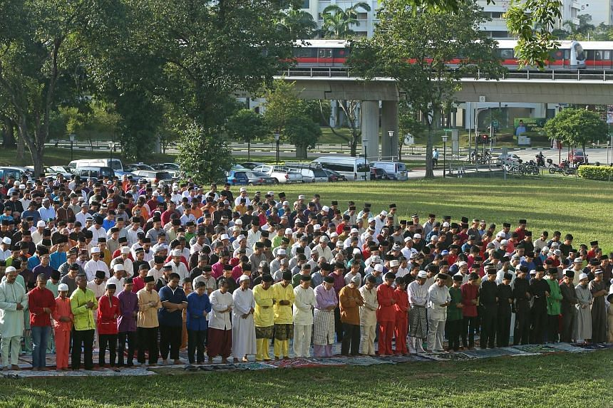 Muslims gathering at a field in Woodlands Street 13 for morning prayers yesterday on Hari Raya Aidilfitri. This is the eighth year that An-Nur Mosque has organised a prayer session in a public area.