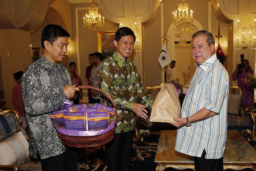 Minister in the Prime Minister's Office Chan Chun Sing (centre) and Minister for Social and Family Development Tan Chuan-Jin (left) attending the Hari Raya Open House hosted by Sultan Ibrahim Ibni Almarhum Sultan Iskandar yesterday at the Istana Buki