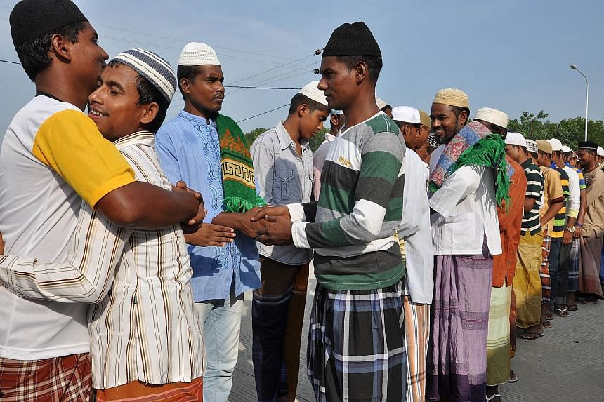 Muslim families in Manila eat in a restaurant after attending prayers at the nearby Golden Mosque. Rohingya and Bangladeshi migrants greet each other after morning prayers at a confinement camp in Langsa, in Aceh province. Pakistanis crowding a bus i