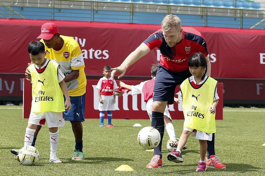 The Straits Times gave 40 out of 65 children between the ages of six and 12 a chance to play with Arsenal stars, including Per Mertesacker (above) and Mesut Oezil, at the Emirates Football Clinic. Faith Lim, seven, was one of the lucky ones. She said
