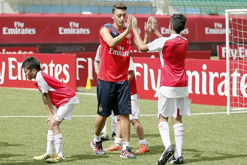 Mesut Oezil at an Emirates clinic yesterday. He and manager Arsene Wenger dismissed the notion that he is unhappy at Arsenal.