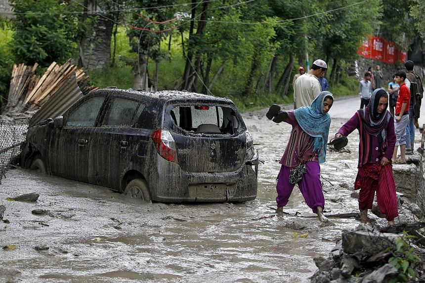 Kashmiri villagers walking through the cloudburst-hit area of Kullan village in the Ganderbal district yesterday. According to local media, at least four people were killed yesterday in a series of cloudbursts that were reported to have hit several p