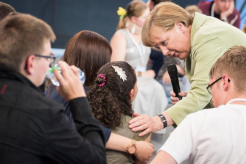 In a video that has gone viral online, German Chancellor Angela Merkel is seen listening sympathetically to a tearful Palestinian girl, Reem, who pleads for her family to be allowed to stay in Germany. The girl's plea puts a human face to the dilemma