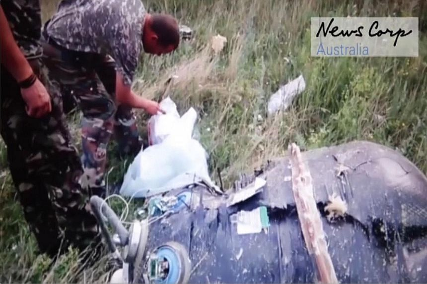 "This screen grab, taken from a video released by News Corp Australia yesterday, allegedly shows Russian-backed rebels looking at what is apparently one of the ""black boxes"" of the Malaysia Airlines plane shortly after it crashed near the village of G"