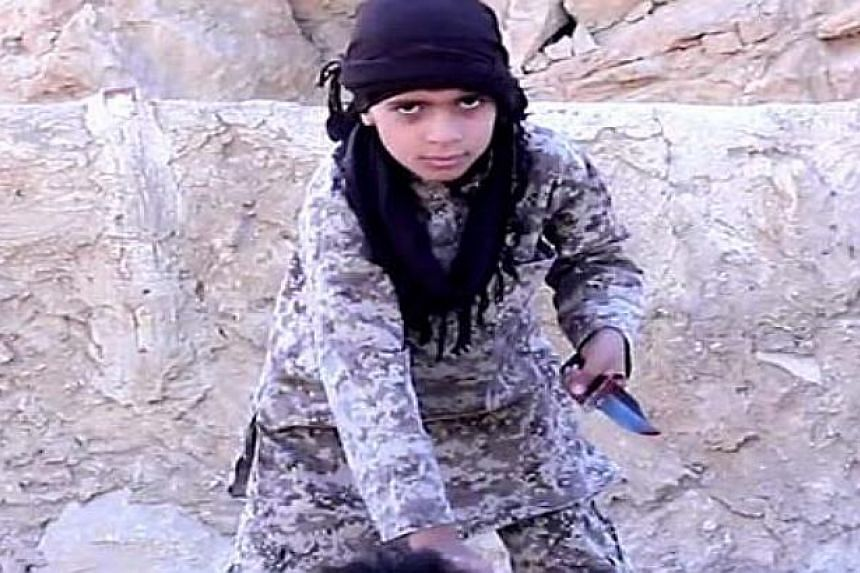 A screenshot from the video in which a child is said to behead a captive soldier.