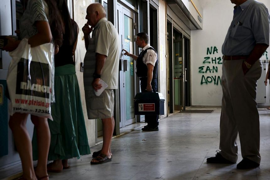 A security worker brings money to a National Bank branch in Athens, Greece on July 17, 2015.