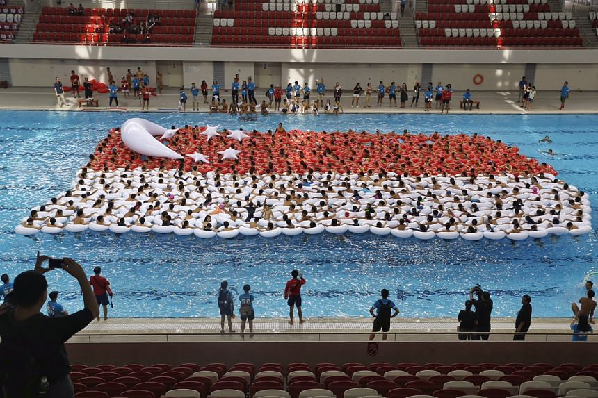 500 swimmer-students attempt to set the record for Largest Floating Singapore Flag during a full rehearsal of 'Youth Celebrate!' to commemorate SG50 at the OCBC Aquatic Centre on July 18, 2015.