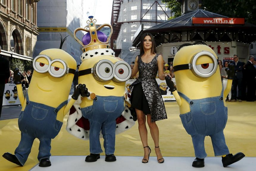 Actress Sandra Bullock poses with characters in costume from the film Minions during the movie's premiere in London.