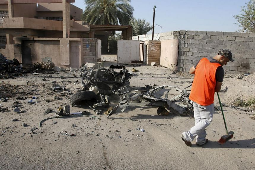 A municipality worker sweeps the ground at the site of a previous car bomb attack in Baghdad on July 13, 2015.