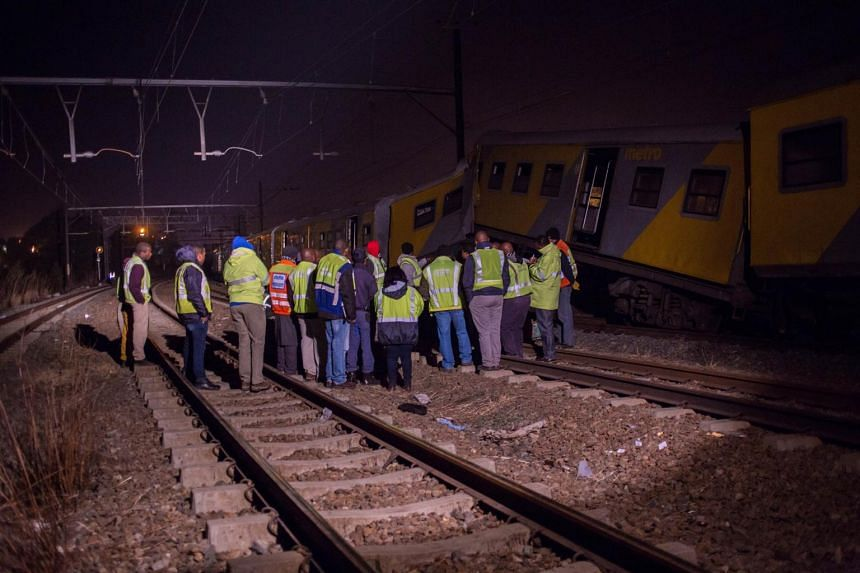 Railway inspectors and emergency personnel stand near the site of a train crash in Johannesburg on July 17, 2015.