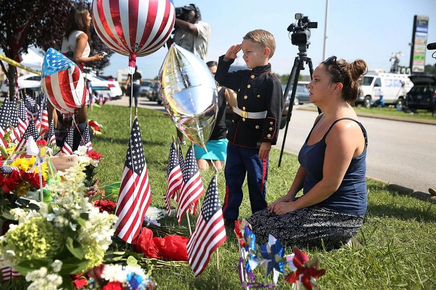 Blake Miller and his mother Ashley Miller, whose husband is a Lieutenant in the Marine Corps, pay their respects to those killed at a memorial in Chattanooga.