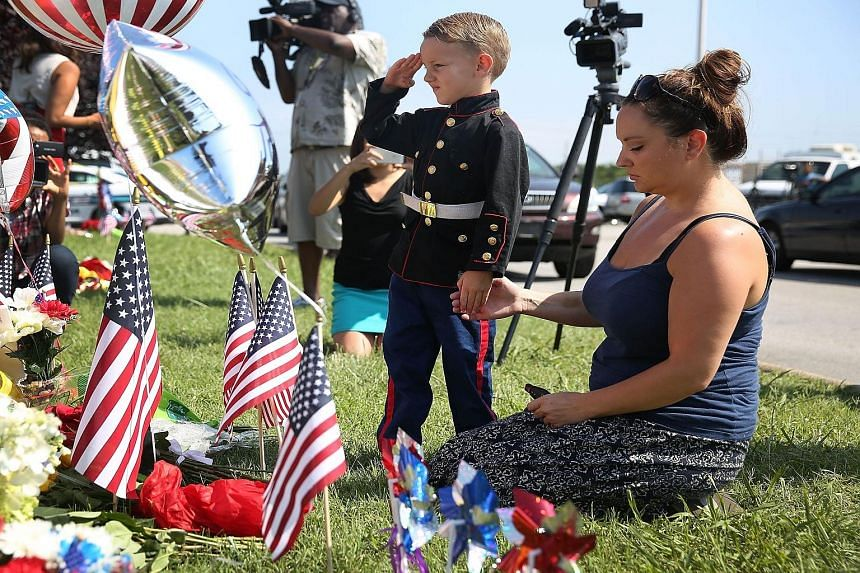 Blake Miller and his mother Ashley paying their respects to those killed while visiting a memorial in front of the Armed Forces Career Centre/National Guard Recruiting Office, which was one of the sites where the shootings took place.