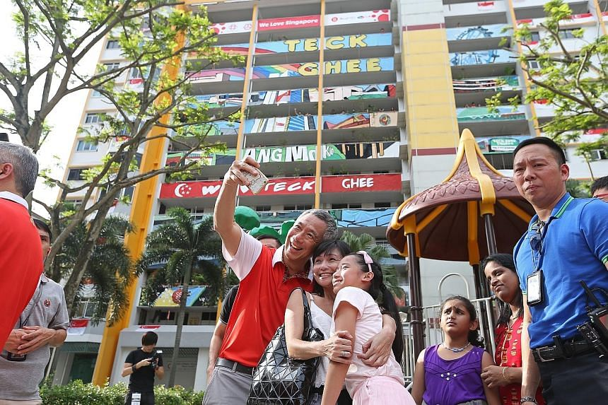 PM Lee Hsien Loong taking a wefie with residents in his Teck Ghee ward. He added the finishing touches to a canvas painting used to complete an art facade (background) on one of the HDB blocks.