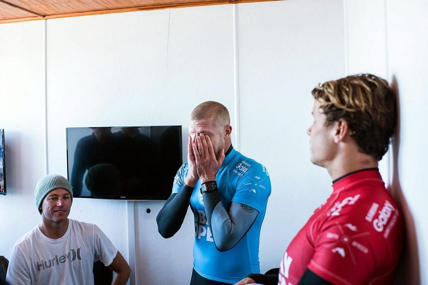 Mick Fanning (centre) covering his face with his hands in the aftermath of the shark attack.