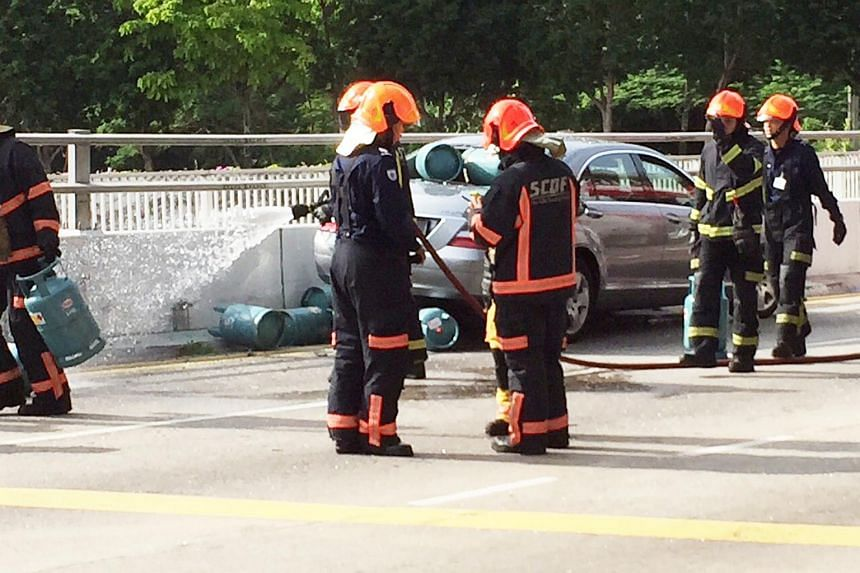 SCDF personnel spraying water on the car after gas canister fell off the lorry and smashed through the car's rear window.