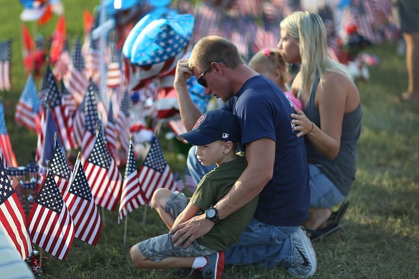People pay their respects at a memorial in front of the Armed Forces Career Centre/National Guard Recruitment Office on July 18, 2015 in Chattanooga, Tennessee.