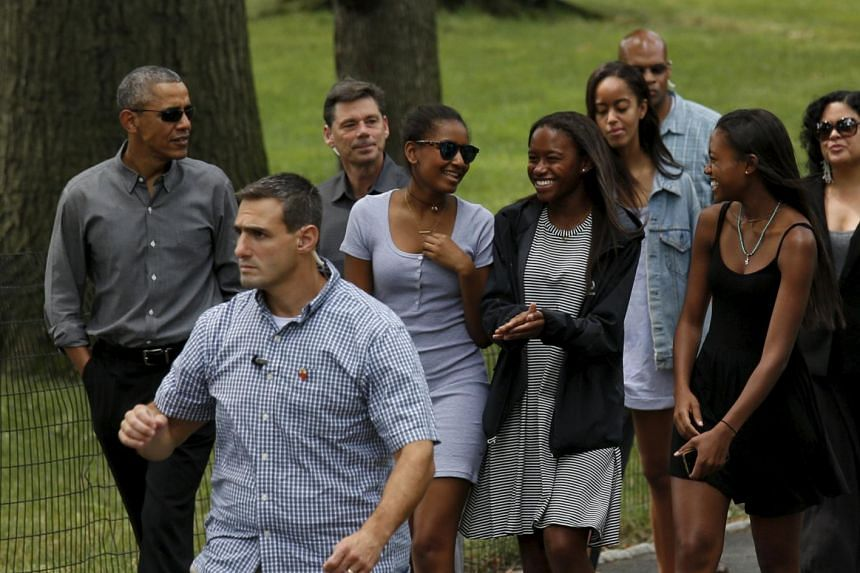 Obama walks in Central Park with daughters Sasha (fourth left), Malia (third right) and friends in New York.