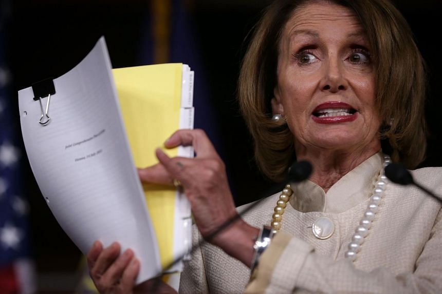 US House Minority Leader Rep Nancy Pelosi holding up a copy of the Joint Comprehensive Plan of Action of the Iran nuclear deal.