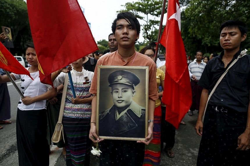 People hold General Aung San's portrait as they wait to pay respect during an event marking the anniversary of Martyrs' Day outside the Martyrs' Mausoleum in Yangon on July 19, 2015.