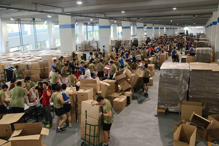 Singapore Army personnel packing funpacks. They aim to to maintain their whopping target of packing up to 120,000 funpacks daily.