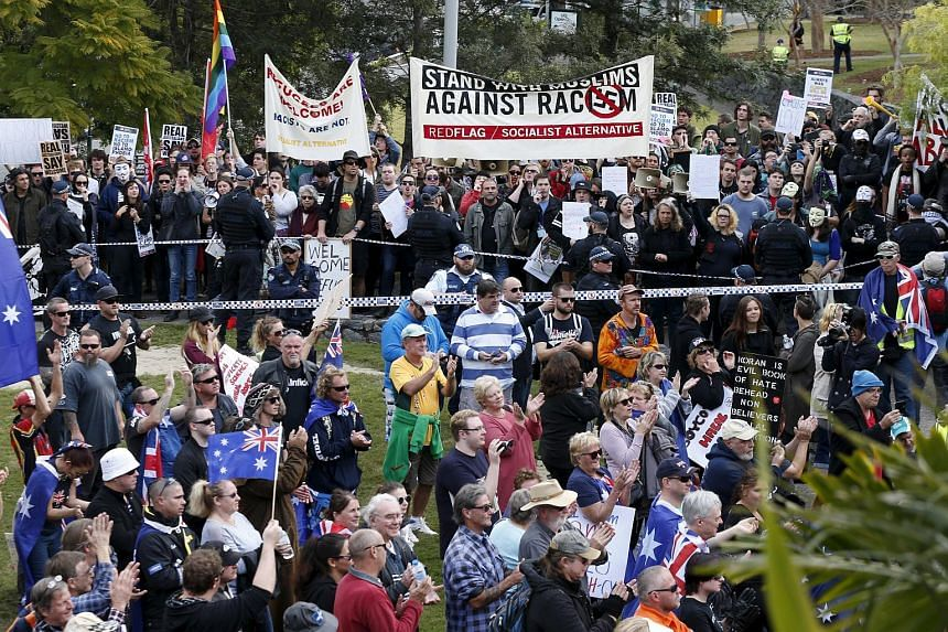 "Opposing protest groups, from the ""Reclaim Australia"" anti-islam group (foreground) and those calling for an end to racism are separated by a police line in Brisbane."