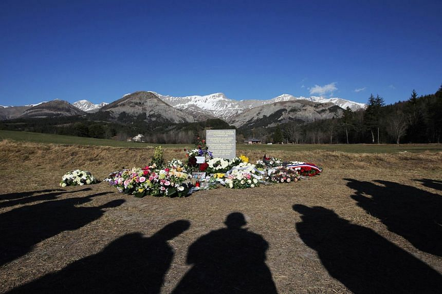 People stand near a stela commemorating the victims of the March 24 Germanwings Airbus A320 crash in the village of Le Vernet, southeastern France.
