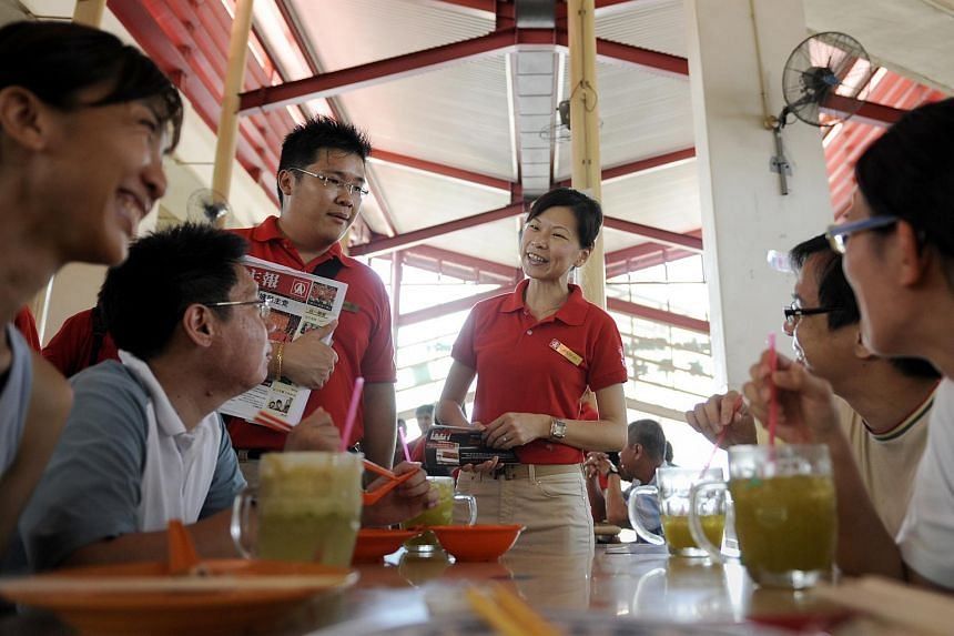 Singapore Democratic Party (SDP) members Jaslyn Go (centre, in red, standing) and Jarrod Luo (left, standing) meeting residents during a walkabout in Yuhua single-member constituency.