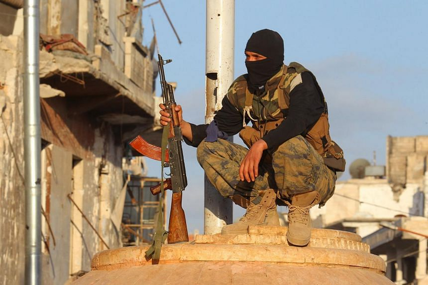 A member of al Qaeda's Nusra Front carries his weapon as he squats in the town of the northwestern city of Ariha.