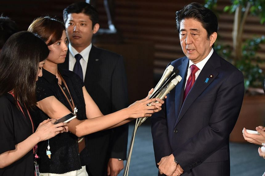 Shinzo Abe speaks (right) during a short press conference after a meeting concerning the 2020 Olympic Stadium, at his official residence in Tokyo.