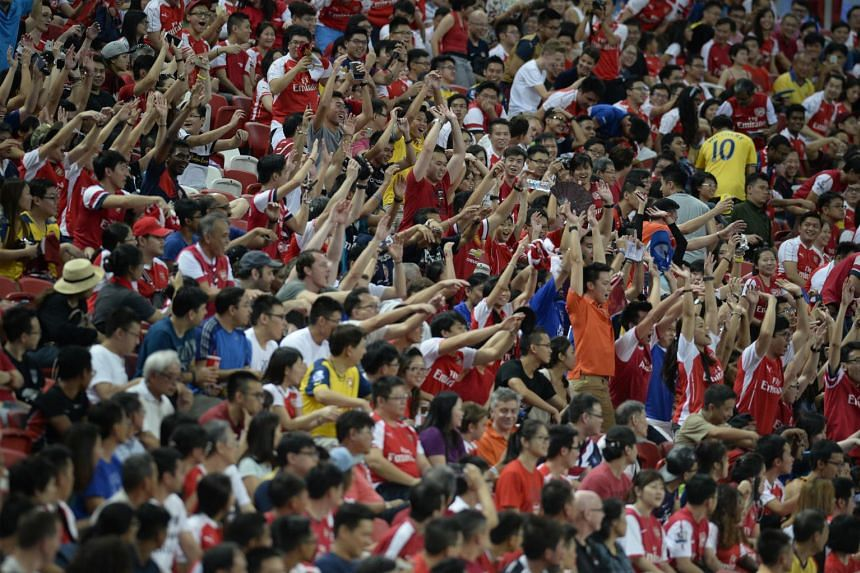 The crowd does the Kallang Wave during the match between Stoke City and the Singapore Selection.